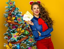 Smiling woman near Christmas tree with envelope and postcard Royalty Free Stock Photo