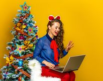 Smiling woman near Christmas tree having video chat on laptop Royalty Free Stock Photos