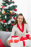 Smiling woman near Christmas tree with present Royalty Free Stock Photo