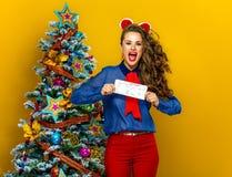 Smiling woman near Christmas tree showing flight tickets. Festive season. smiling stylish woman near Christmas tree isolated on yellow background showing flight Royalty Free Stock Image