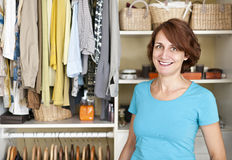 Smiling woman near closet. Happy woman standing in front of custom organized closet at home stock photos