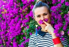 Smiling woman near colorful magenta flowers bed having fun time. Colorful Freshness. Portrait of smiling stylish woman in stripy shirt near colorful magenta Royalty Free Stock Photography