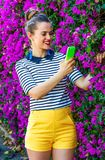 Smiling woman near flowers bed taking photo with cellphone. Colorful Freshness. smiling stylish woman in yellow shorts and stripy shirt against colorful magenta Royalty Free Stock Photo