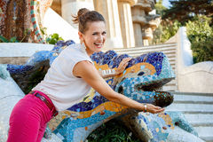 Smiling woman near mosaic dragon in Park Guell, Spain Royalty Free Stock Photos