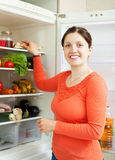 Smiling woman near refrigerator Royalty Free Stock Photo