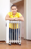 Smiling woman  near warm radiator Royalty Free Stock Image