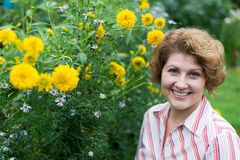 Smiling woman near yellow flowers in nature stock photography