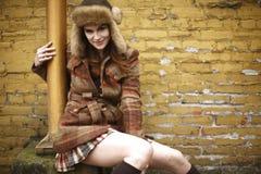 Smiling woman next to brick wall Royalty Free Stock Image