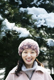 Smiling woman next to tree covered in snow, portrait Royalty Free Stock Photos