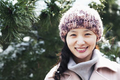 Smiling woman next to tree covered in snow, portrait Royalty Free Stock Images
