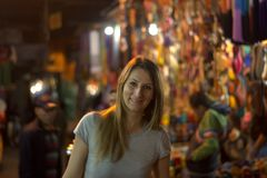 The smiling woman in the night among the stalls of the medina. Traveling in the colors and scents of the East Royalty Free Stock Photo
