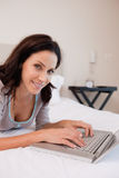 Smiling woman with notebook on the bed Royalty Free Stock Photo