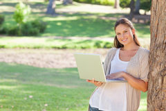 Smiling woman with a notebook leaning against a tree Stock Images