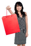Smiling woman offering bag full of gifts Stock Photo