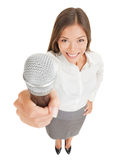 Smiling woman offering up a microphone. Fun high angle perspective of a beautiful smiling young woman offering up a microphone with her hand raised towards the stock photo