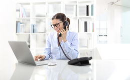Smiling woman in office at desk with computer and phone. Smiling woman in office at desk with computer, talking on the phone Royalty Free Stock Images