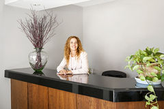 Smiling woman at office reception. Receptionist standing at reception counter in office Royalty Free Stock Image