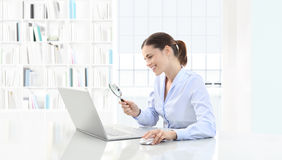 Smiling woman in office search on computer with magnifying glass. Sitting at the desk Stock Photography