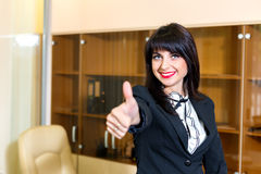 Smiling woman in office shows thumb up Royalty Free Stock Photo