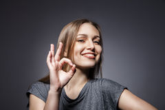 Smiling woman with okay gesture on dark grey Royalty Free Stock Photography