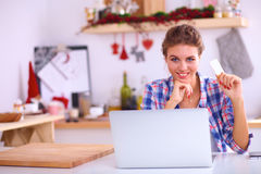 Smiling woman online shopping using computer and Stock Photography