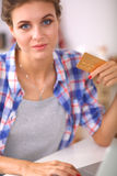 Smiling woman online shopping using computer and credit card in kitchen Royalty Free Stock Photography