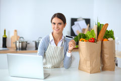 Smiling woman online shopping using computer and credit card in kitchen Stock Photos