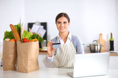 Smiling woman online shopping using computer and credit card in kitchen Stock Photography