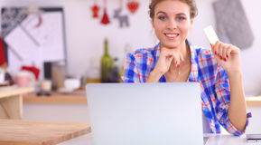Smiling woman online shopping using computer and credit card in kitchen Stock Image