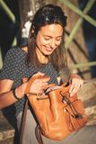 Smiling woman opening a backpack while sitting stock photo