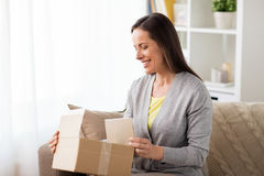 Smiling woman opening cardboard box royalty free stock photo