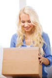 Smiling woman opening cardboard box at home. Transportation, delivery, home and people concept - smiling woman opening cardboard box at home royalty free stock image