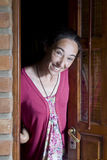 Smiling woman opening the door Royalty Free Stock Photos