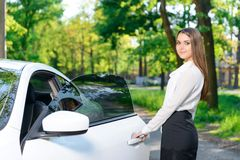 Smiling woman opening door of car Royalty Free Stock Images