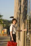 Smiling Woman Opening Door - Vertical Stock Image