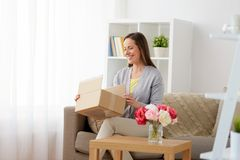 Smiling woman opening parcel box at home Stock Image