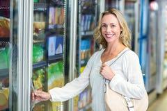 Smiling woman opening supermarket fridge. Side view of smiling woman opening supermarket fridge royalty free stock photo