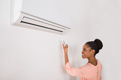 Smiling Woman Operating Air Conditioner Stock Photo