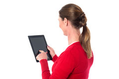 Smiling woman operating touch pad device. Lady placing her finger on the screen of touch pad device Royalty Free Stock Photo