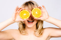 Smiling woman with orange. In both hands Royalty Free Stock Images