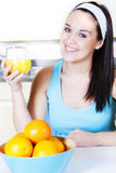 Smiling woman with orange juice in the kitchen Stock Image