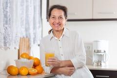 Smiling  woman  with orange juice in   kitchen. Middle-aged woman preparing orange juice royalty free stock image