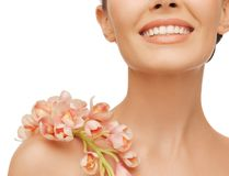 Smiling woman with orchid flower on her shoulder Stock Photo
