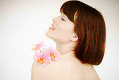 Smiling woman with an orchid on her arm stock photography
