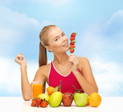 Smiling woman with organic food eating strawberry Stock Photos