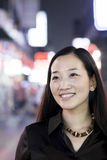 Smiling woman out at night in the city, portrait Royalty Free Stock Photos