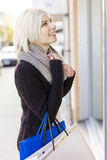 Smiling woman out shopping in the city. Smiling young woman standing outside a shop and looking at the goods in the window Royalty Free Stock Images