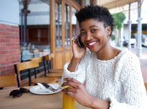 Smiling woman at outdoor restaurant with mobile phone Royalty Free Stock Image