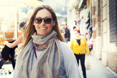 Smiling woman outdoor, with scarf and sunglasses royalty free stock image