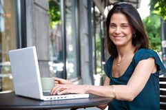 Smiling woman outdoors with laptop Stock Photos